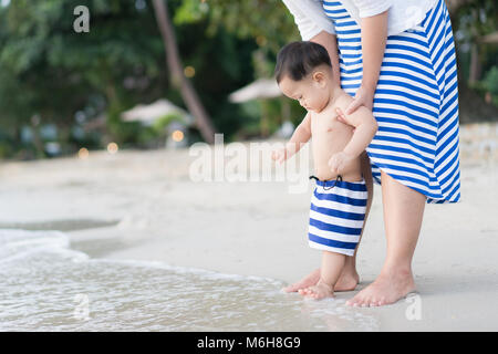 Asian Toddler baby boy with mother doing his first steps on the sand near the bank - Stock Photo