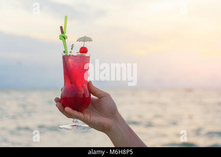 Hand holding red cocktail drink in twilight sea & sky background. Summer, Vacation, Travel and Holiday concept. - Stock Photo