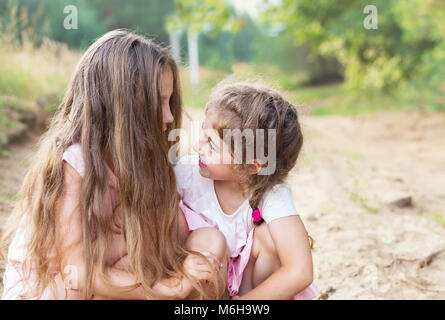 Beautiful young girls with long hair; smiling and talking at summer - Stock Photo
