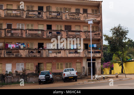 Bissau, Republic of Guinea-Bissau - January 28, 2018: An old and crumbling apartment building with goats at its - Stock Photo