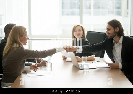 Smiling businessman and businesswoman shaking hands at diverse t - Stock Photo