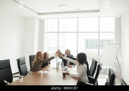 Happy businesspeople giving high-five at office meeting, celebra - Stock Photo