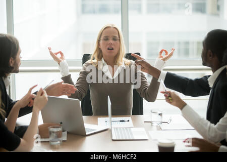 Stressed businesswoman meditating at meeting with diverse employ - Stock Photo