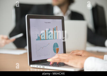 Businesswoman working with statistical report at team meeting an - Stock Photo