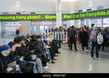 Passengers await the next Staten Island Ferry departure at Whitehall Terminal in Lower Manhattan, NYC, USA - Stock Photo