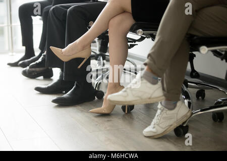 People sitting in row, men and women waiting in queue - Stock Photo
