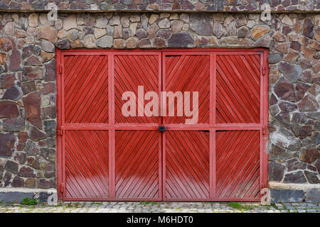 Old red wooden gate with lock in a stone fence - Stock Photo