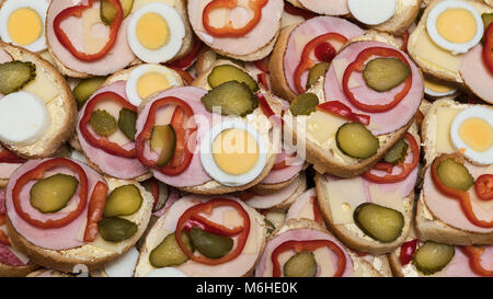 Open-face sandwiches as gastronomic background. Colorful texture from slices of french bread with ham, cheese, hard - Stock Photo