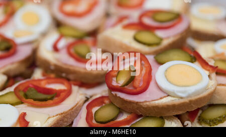 Open-face sandwiches with sausage and vegetables as background. Close-up of white bread slices with ham, cheese, - Stock Photo