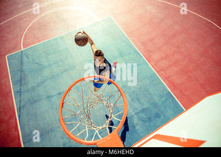 High angle view of basketball player dunking basketball in hoop - Stock Photo