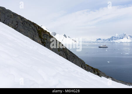 A ship anchored in Paradise Bay, Antarctica with snow and a ridge of rock in the foreground and the bay, ship and - Stock Photo