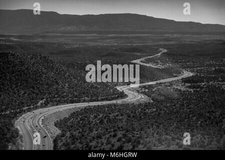 An expansive aerial landscape of an Arizona Highway winding through a grand forest, taken from a helicopter. - Stock Photo