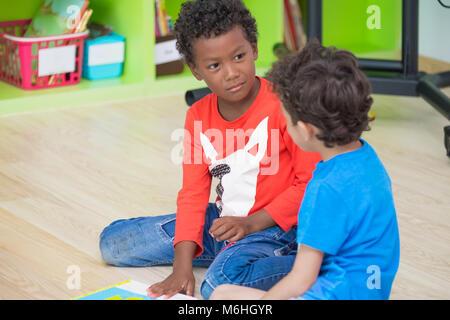Two boy kid  sitting on floor and taking in preschool library,Kindergarten school education concept.diversity children