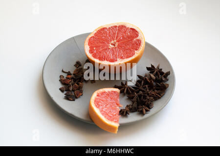 Fresh grapefruit slices and heap of star anise species isolated on grey concrete plate - Stock Photo
