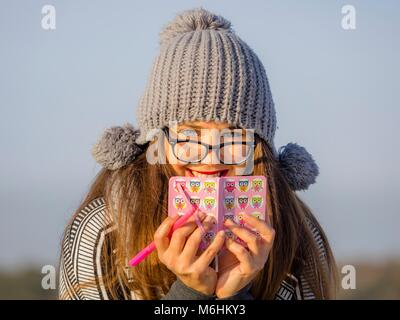 Pretty young woman portrait with Gray Winter cap and spectacles grasping grasp - Stock Photo