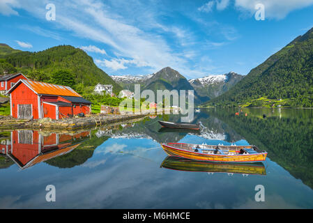 boats and red fishermen hut, Norway, seashore and bay of Balestrand with mirroring of glacier mountains, Esefjorden, - Stock Photo