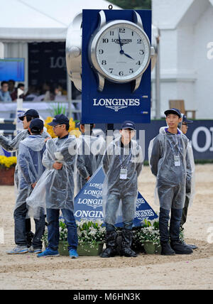 Staff wait for the rain to stop at the FEI jumping event in Chaoyang park, Beijing, China, in October 2016 - Stock Photo