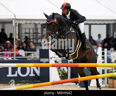 China's Ciren Bianba with Montendro competes at the FEI jumping event in Chaoyang park, Beijing, China, in October - Stock Photo