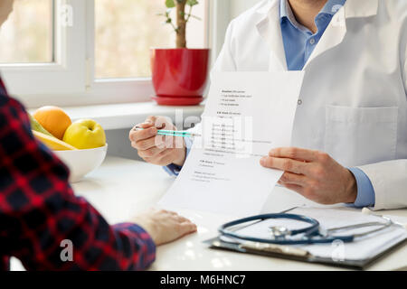nutritionist and patient discussing balanced nutrition plan in office - Stock Photo