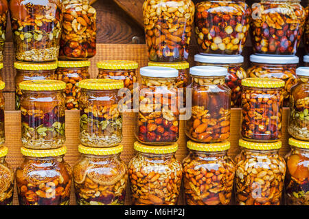 Colorful honey with fruit and nuts canned  in the glass  jar, on a market. - Stock Photo