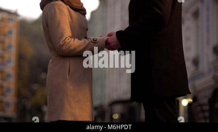 Married couple holding hands tenderly, still in love, romantic walk in big city - Stock Photo