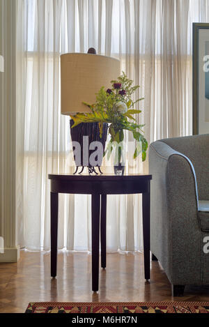 Interior shot of  table lamp and colorful flowers planter on small dark brown wooden table on background of big - Stock Photo