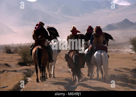 Four Kazakh eagle hunters on horseback making their way to the 2017 golden eagle festival where they will compete. - Stock Photo