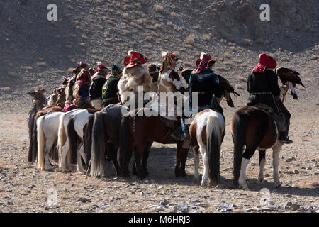Kazakh eagle hunters on horseback on display at the parade of competitors at the beginning of the 2017 golden eagle - Stock Photo