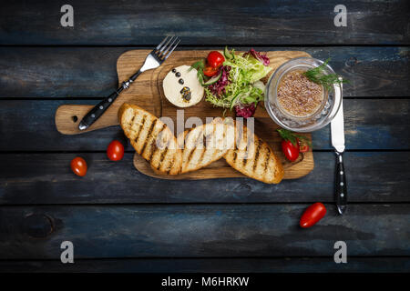 Toast with butter and caviar served with cutlery on a wooden background - Stock Photo