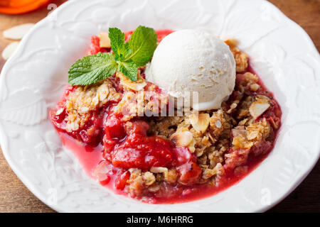 Crumble with berries and fruits with vanilla ice cream. - Stock Photo