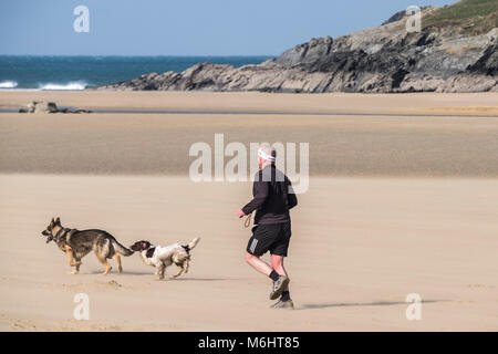 A man running with his dogs on Crantock Beach in Newquay Cornwall.