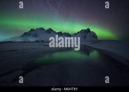Green reflections in the snow in Stokkness, Iceland - Stock Photo