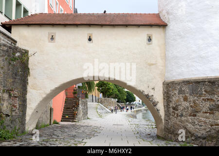 Stone arch over cobblestone pedestrian street. A popular path along the Danube river in Passau, Germany. - Stock Photo