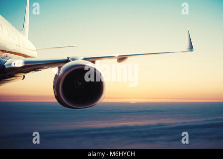 Aircraft flight over the clouds during sunrise - Stock Photo