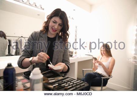 Female makeup artist preparing makeup for model, preparing for photo shoot - Stock Photo