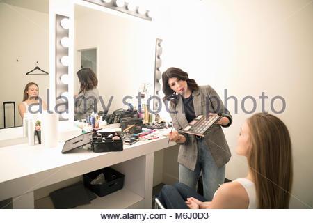 Female makeup artist applying makeup to model, preparing for photo shoot - Stock Photo