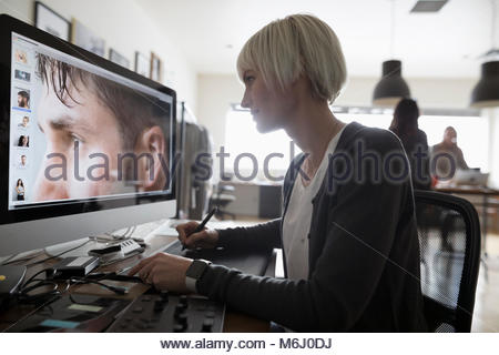 Female photo editor using graphics tablet, editing digital photograph on computer in office - Stock Photo