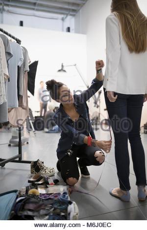Female wardrobe stylist measuring model for photo shoot in studio - Stock Photo
