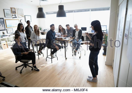 Female production manager leading production team meeting in office - Stock Photo