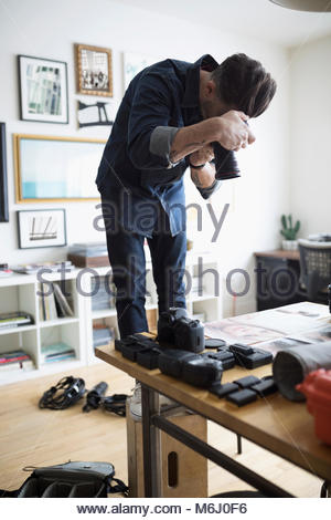Male photographer standing on box, using digital camera in office - Stock Photo