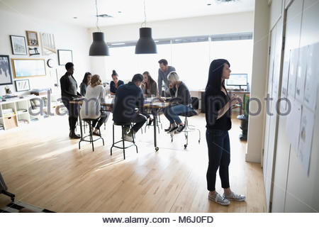 Female photo editor reviewing photo proofs hanging on office wall - Stock Photo
