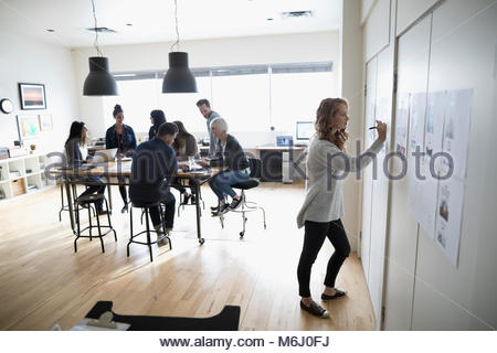 Female photo editor with digital tablet editing photo proofs hanging on office wall - Stock Photo