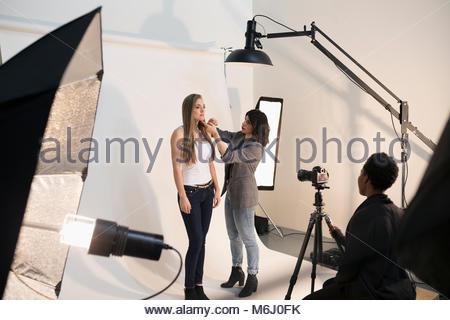 Female makeup artist applying makeup to model, preparing for photo shoot in studio - Stock Photo