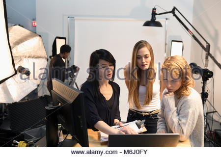 Female production assistants and model at laptop at photo shoot in studio - Stock Photo