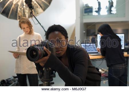 Focused female photographer using digital camera at photo shoot in studio - Stock Photo