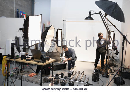 Photographer and production assistant preparing lighting equipment for photo shoot in studio - Stock Photo