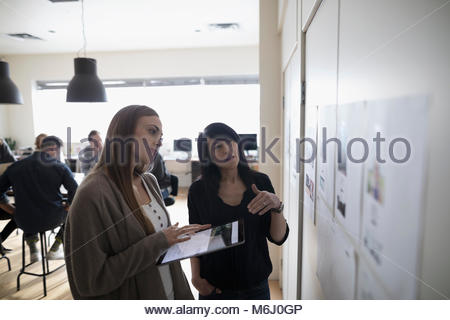 Female photo editors with digital tablet discussing photo proofs hanging on office wall - Stock Photo