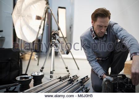 Male photographer preparing equipment for photo shoot in studio - Stock Photo