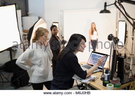 Female photographer and production assistants using computer and laptop at photo shoot in studio - Stock Photo