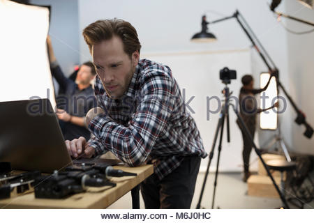 Male production manager using laptop at photo shoot in studio - Stock Photo